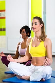 더 나은 피트니스, 백인 및 라티 나 사람들을 위해 체육관에서 요가와 명상을하는 젊은 여성