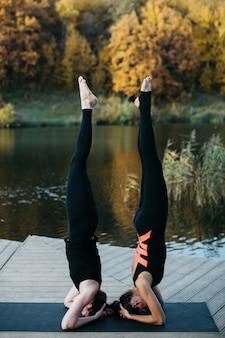 湖の近くの自然の中でヨガのアーサナをしている若い女性