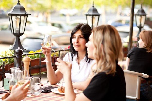 카페 테라스에서 화이트 와인을 마시는 젊은 여성.