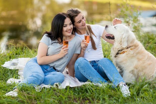 屋外の犬の横に飲む若い女性