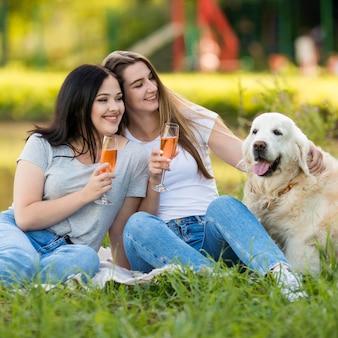 外の犬の横に飲む若い女性