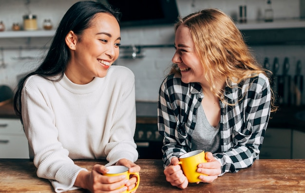Young women drinking tea and smiling