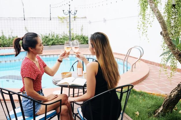 Молодые женщины пьют вино за столиком в кафе