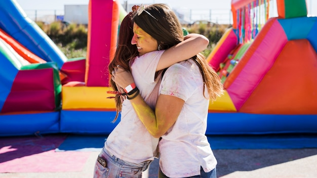 Young women embracing each other celebrating the holi festival