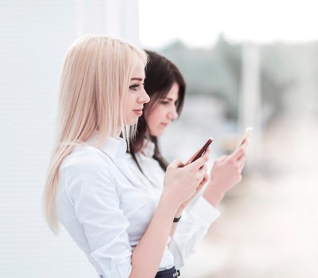 Молодые женщины-сотрудники компании обмениваются информацией на смартфоне