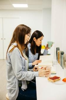 Молодые женщины, наслаждаясь завтраком и чтением
