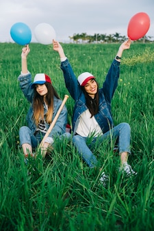 Young women enjoying Independence Day in field with balls