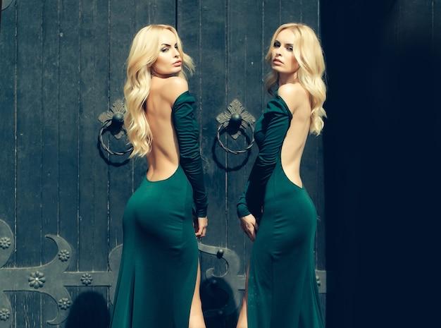 Young women in fashion dress standing near big door