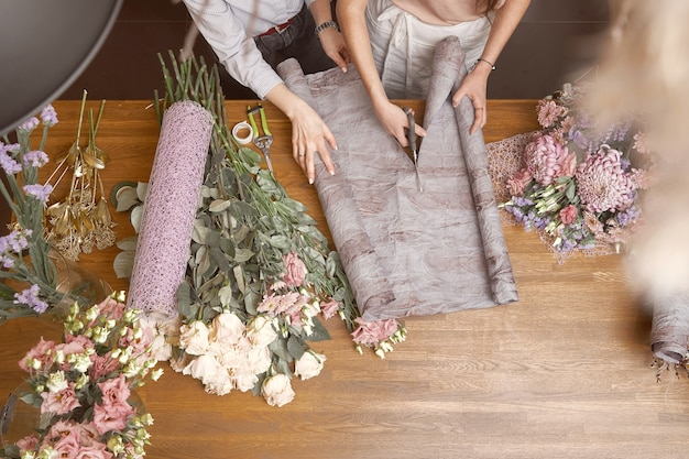 彼女のスタジオで美しい花束を作っている若い女性の花屋。上面図