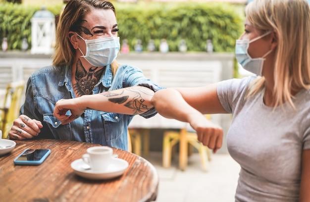 Молодые девушки-подруги хлопают локтями вместо того, чтобы приветствовать их объятиями