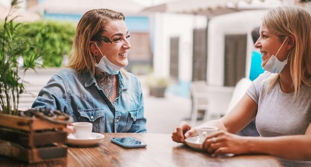 Друзья молодых женщин пьют кофе в баре во время пандемии коронавируса