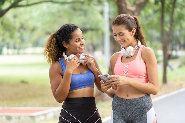 公園で一緒にジョギングしている若い女性の友人。ジョギングしながら音楽を聴く女性ランナー。