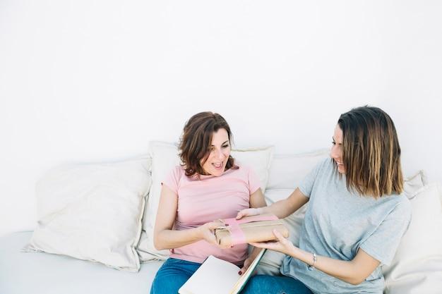 Молодые женщины, дающие подарок женщине дома