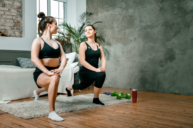 젊은 여성들이 집에서 스포츠를하고 온라인으로 운동을합니다.