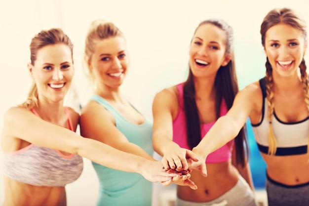トレーニング後にジムでハイタッチをする若い女性グループ