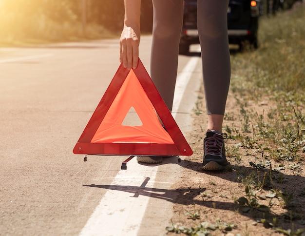 젊은 여성의 손이 길가에 부서진 차 근처 도로에 삼각형 주의 표지판을 두는 것을 닫습니다.