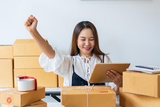 電子メールで顧客から大きな注文を受けた後、若い女性は幸せです。オンラインショッピング、自宅での仕事、自宅での仕事、ビジネスとテクノロジー、中小企業の起業家のコンセプト。