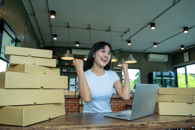 Молодые женщины счастливые после нового заказа от клиента, владельца бизнеса работая дома офис упаковывая на предпосылке, онлайн продажах, или электронной коммерции. концепция продаж.