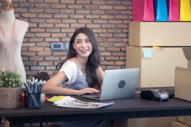 若い女性は、顧客、バックグラウンドでホームオフィスのパッケージング、オンライン販売で働いているビジネスオーナーからの新しい注文の後に幸せです。