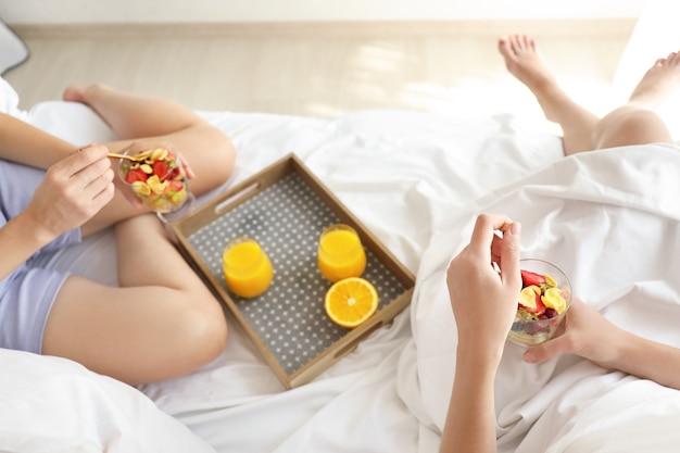 침대에서 맛있는 아침 식사를하는 젊은 여성