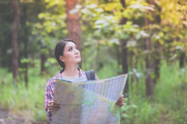 Молодые женщины-туристы, которые смотрят на карте и время отдыха в отпуске