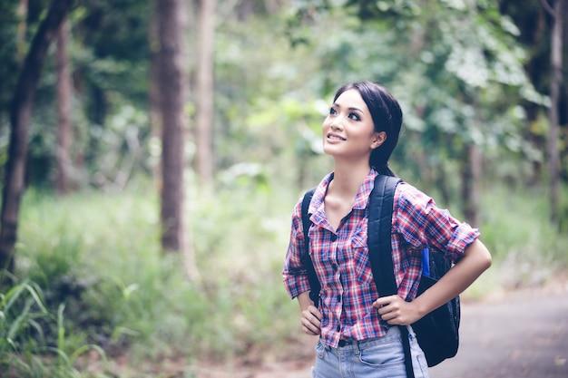若い女性のハイカーは休日のコンセプト旅行の時間をリラックスして森林