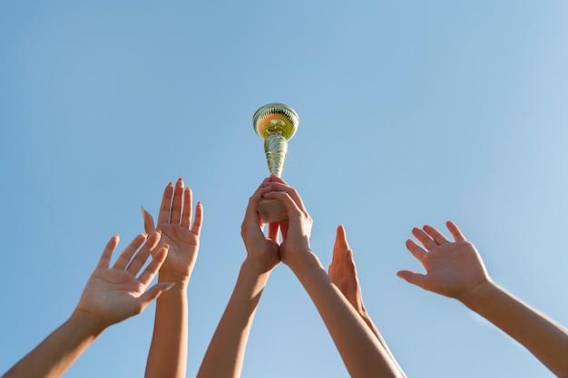 スポーツカップを保持している若い女性