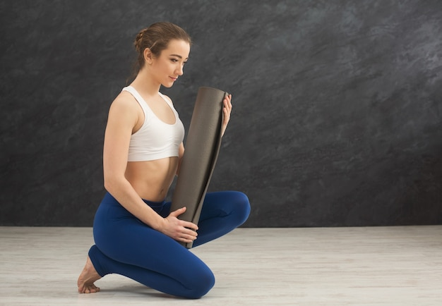 トレーニング時間にジムでトレーニングクラスのために灰色のヨガマットを保持している若い女性。ヨガの練習の前後のスポーツクラブ。コピースペース