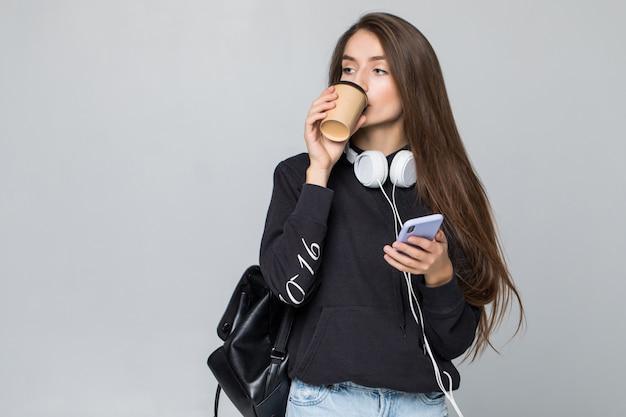 スマートフォンと一杯のコーヒー、白い壁で隔離を保持している若い女性