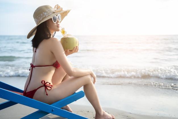 Молодые женщины в бикини отдыхают на пляже