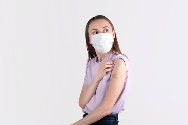Молодые женщины в маске для лица с лейкопластырем после вакцинации