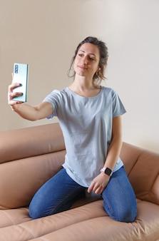 自宅で携帯電話で自分撮りをする眼鏡と青いtシャツの若い女性