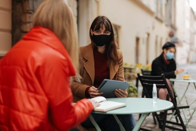 オープンエアのテラスで遠くに座っている医療マスクの若い女性。現代のガジェットを使用し、本を話したり読んだりする人々。コロナウイルスの概念。