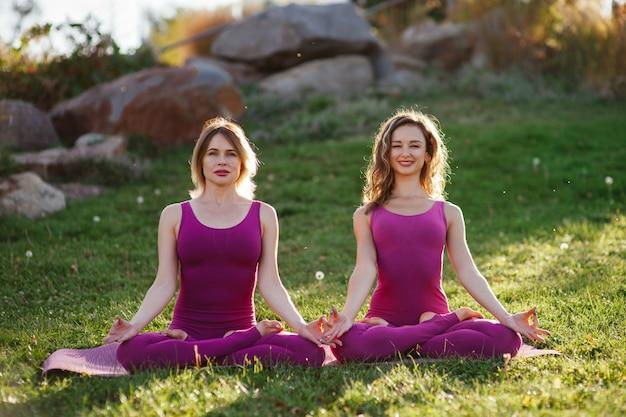 Молодые женщины в фиолетовой спортивной одежде тренируются вместе на траве
