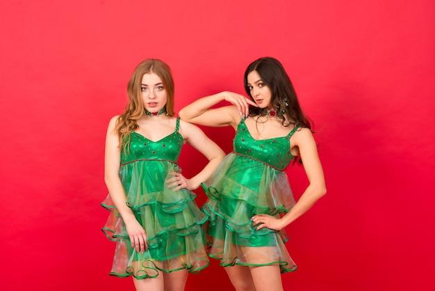 スタジオの赤い壁にセクシーなクリスマス ツリーの衣装を着た若い女性