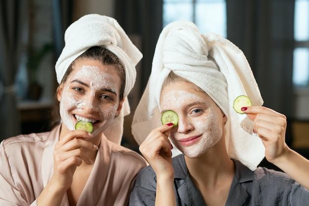 シルクのパジャマを着た若い女性、頭にタオル、顔に粘土のマスク、目のキュウリのスライスを楽しんで、美容の手順を楽しんでいます