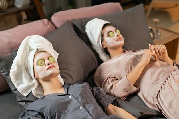 シルクのパジャマを着た若い女性、頭にタオル、顔に粘土のマスク、目を閉じてキュウリのスライスをベッドで美容の手順を楽しんでいます