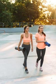 미소하고 피트니스 매트가있는 운동장에서 운동복을 입은 젊은 여성