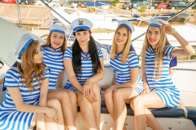 Молодые женщины в полосатых платьях и кепках, на палубе яхты, концепция отдыха на яхте.