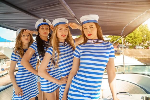 ヨットの甲板上の縞模様のドレスと帽子の若い女性、ヨットでのレクリエーションの概念。
