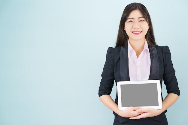 青い背景に立っている彼女のデジタルタブレットを保持しているスーツの若い女性