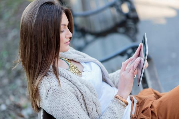 Молодые женщины в парке с планшетом