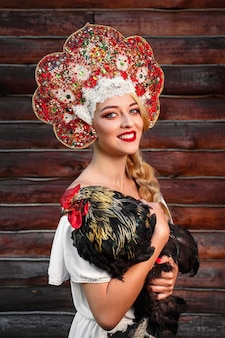 Молодые женщины в красном головном уборе и русском народном стиле держат петуха на темном дереве. русская сказка