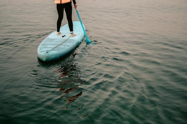 ビーチのsupボードパドルボードの背景にオールを漕ぐサーモ服の若い女性supボード