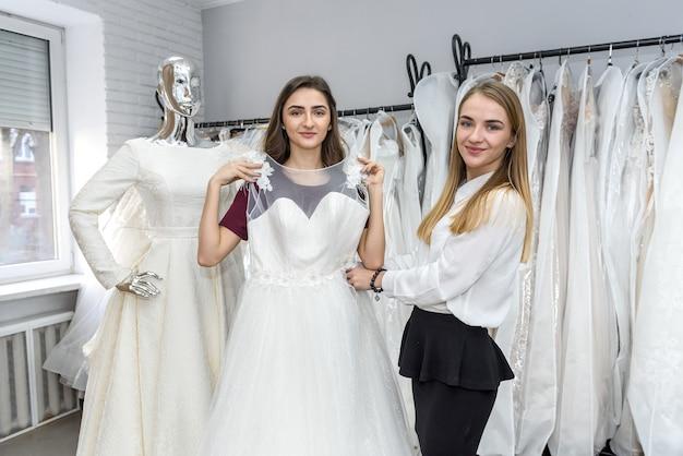 ドレスを選ぶ結婚式のサロンの若い女性