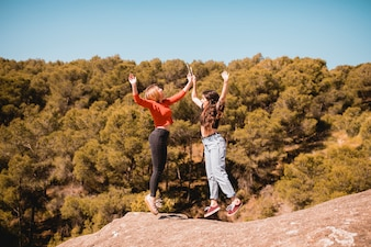 Young women jumping on cliff