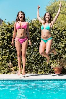 수영장의 가장자리에 점프하는 젊은 여성