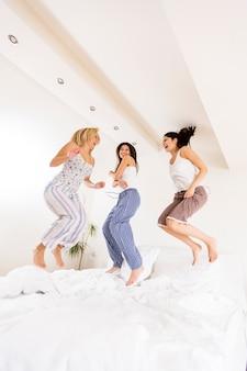 침대에서 점프하는 젊은 여성