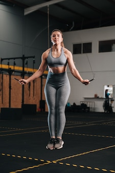 강렬한 운동을하는 동안 밧줄 점프하는 젊은 여성