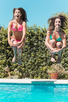Young women jumping in swimming pool